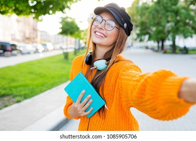 Cheerful pretty brunette girl making self portrait by mobile phone in sunny park. Holding books.
