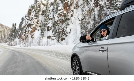 Cheerful pretty brunette sitting in a car and showing thumb up sign through opened side window in sunny winter day on icy road close up.