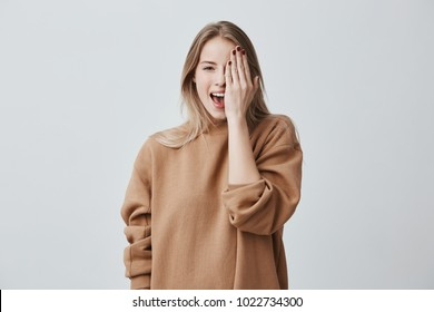 Cheerful pretty charming woman in loose sweater with fair hair smiling happily, having fun indoors, closing one eye with hand. Pretty girl looking at camera with joyful smile
