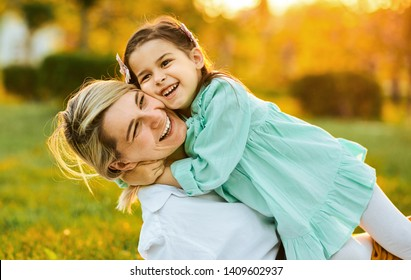 Cheerful pretty daughter smiling with her mother, spending time together in the park. Beautiful young woman playing with her child on the green grass. Mom and little girl shares love.
