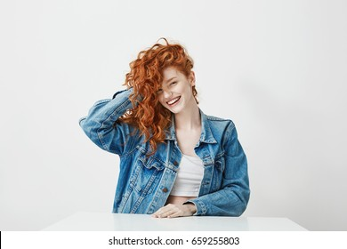 Cheerful pretty girl laughing looking at camera touching her red curly hair over white background.
