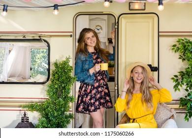 Cheerful pretty girls in bohoo festival dresses at the caravan camping