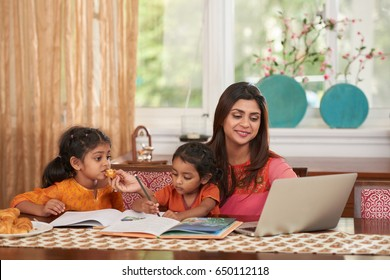 Cheerful pretty Indian woman working on laptop when babysitting
