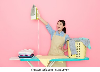 cheerful pretty maid worker holding ironing tool standing in pink background and raised hand shouting cheer up to encourage herself.