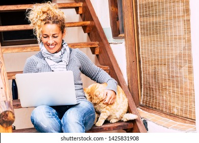 Cheerful pretty middle age woman work with laptop computer outdoor at home with nice cat near her - leisure technology activity and alternative office work lifestyle for independent people