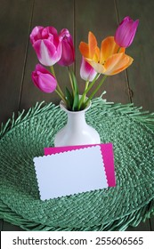 Cheerful and Pretty Orange and Pink Spring Tulips in a White Vase on a  Wood Table and green placemat with Notecard, blank for your words, text, copy.  Vertical looking down from above view,
