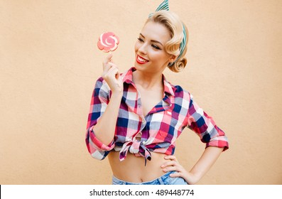 Cheerful pretty pinup girl eating sweet lollipop over pink background