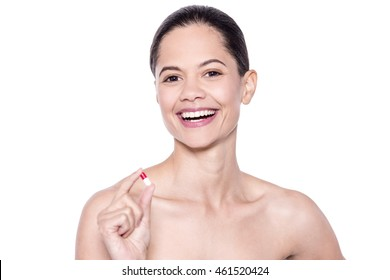 Cheerful pretty undressed lady holding medical pill