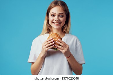 Cheerful pretty woman from a hamburger in the hands of fastfood breakfast diet blue background