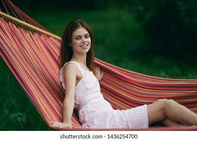 Cheerful pretty woman white dress hammock leisure nature tropics relax lifestyle summe