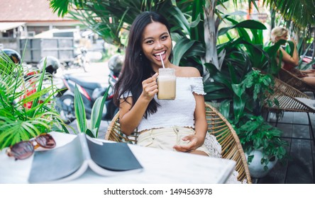 Cheerful pretty young Asian woman in off-shoulder blouse sipping cold coffee from mason jar through straw while sitting at table in open terrace