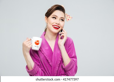 Cheerful pretty young housewife talking on cell phone and drinking tea