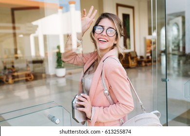 Cheerful pretty young lady entering glass door into modern office, hotel, cafe, business centre and looking back to wave bye. Girl wearing stylish glasses, pink jacket, silver backpack.