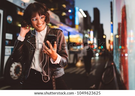 3b646dda5a5 Cheerful pretty young woman in cool eyeglasses and trendy wear walking on  metropolis street with night