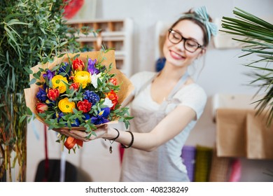 Cheerful pretty young woman florist in glasses showing bouquet of colorful flowers
