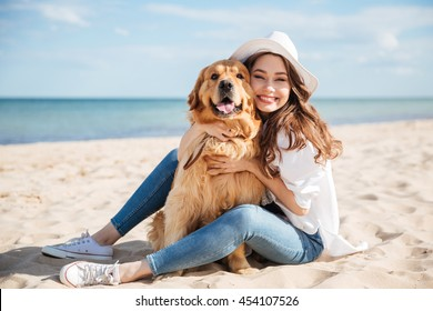 Cheerful pretty young woman in hat sitting and hugging her dog on the beach