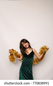Cheerful pretty young woman posing with golden tinsel and looking at camera in studio.