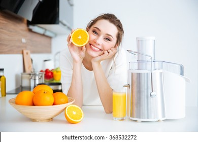 Cheerful pretty young woman showing half of orange sitting on the kitchen