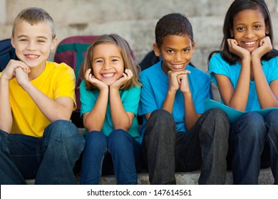 cheerful primary school children sitting outdoors