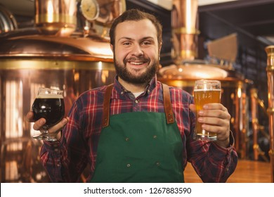 Cheerful professional brewer in an apron smiling happily to the camera holding two glasses of beer, enjoying working at his microbrewery. Happy bartender serving two beers. Friendly service concept