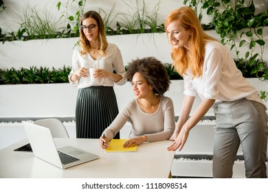 Cheerful professional multiracial women working and presenting data in modern office