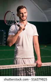 Cheerful professional tennis player holding racket