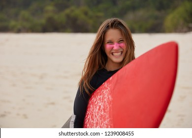 Cheerful professional young female surfer smiles broadly, carries red waxed surfboard, has zinc on face, happy after hiting big ocean wave, models against sand background, expresses positiveness