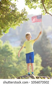cheerful proud little boy holding american flag celebrating 4th of july, independence day, or memorial day