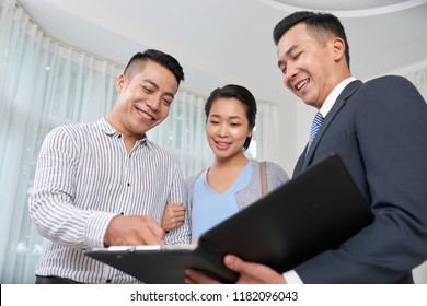 Cheerful real estate agent showing photos of objects to clients