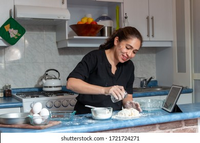 Cheerful real young woman preparing dough for an apple pie in the kitchen at home. Flour, eggs, butter apple