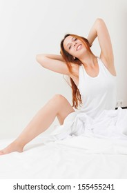 Cheerful red-haired girl in shirt lying on white sheet in bed at home