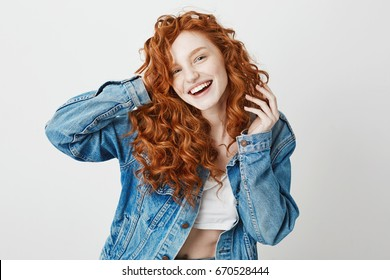 Cheerful redhead girl smiling laughing looking at camera over white background. Copy space.