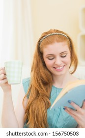 Cheerful redhead reading a book on the couch and holding mug at home in the living room