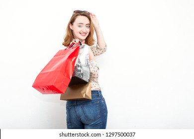 Cheerful redhead woman after shopping holding her bags and standing against light background.