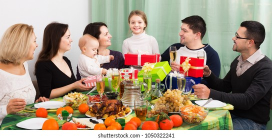 Cheerful relatives wishing little girl happy birthday and giving presents at festive table. Focus on girl
