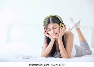 Cheerful relaxing girl with headphone listening to music on her vacation in bedroom. Asian Happy girl enjoy her weekend by songs from mobile phone. Holiday, vacation, lifestyle concept.