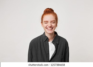 Cheerful resilient red-haired girl with a bun at her head laughs sincerely, having closed her eyes, dressed in a simple black shirt, is isolated on white background