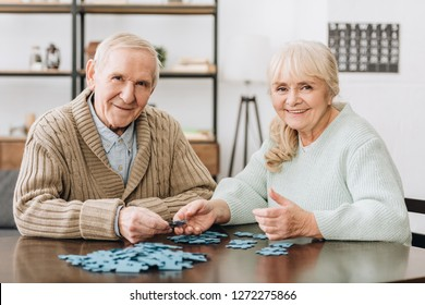 cheerful retired couple playing with puzzles at home