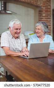Cheerful retired couple typing on laptop in kitchen