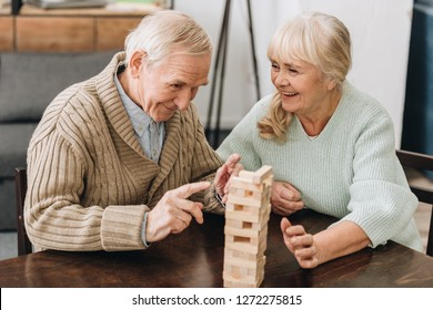 cheerful retired husband and wife playing jenga game on table