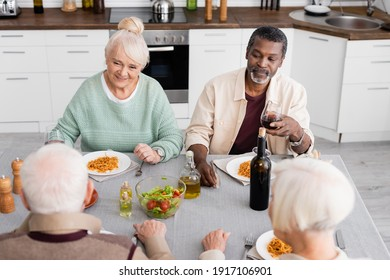 fröhliche und pensionierte interethnische Freunde, die zusammen zu Mittag essen