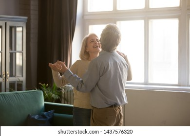 Cheerful retired spouses husband and wife laughing dancing in living room, happy romantic old middle aged couple enjoying slow dance having fun celebrating anniversary or new house purchase at home