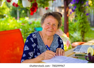 Cheerful retired woman writing about her inheritance in her floral garden.