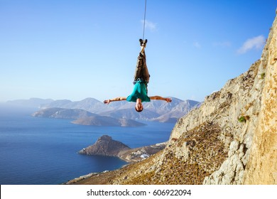 Cheerful rock climber swinging on rope upside down while fooling around