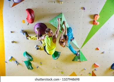 Cheerful rock climbers in bouldering gym climbing on overhanging wall