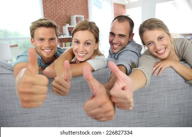 Cheerful roommates showing thumbs up