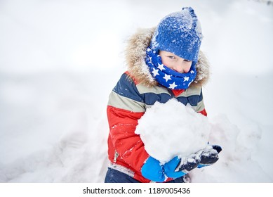 Cheerful ruddy little boy in a snow-capped winter hat, portrait