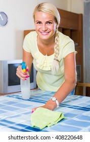 Cheerful russian blonde girl dusting in room and smiling