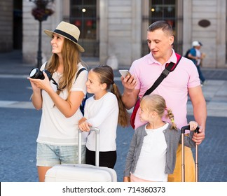 Cheerful russian parents with two kids using smartphone and photographing sights during their travel