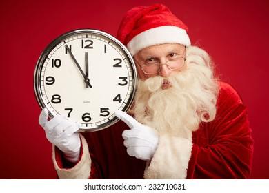 Cheerful Santa pointing at clock in his hand and looking at camera